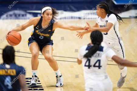 Stock Image of Marquette Golden Eagles guard Rose Nkumu (3) drives past Xavier Musketeers guard Aaliyah Dunham (3) during an NCAA basketball game on in Cincinnati, Ohio