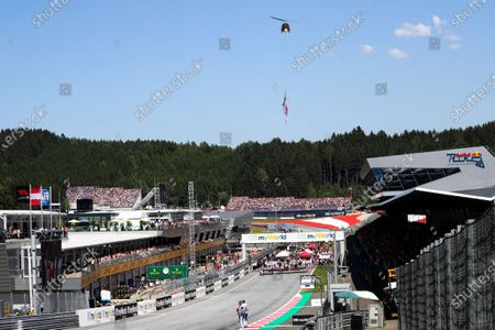 A Helicopter flies a flag paying tribute to the late Niki Lauda prior to the start