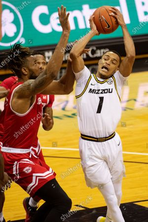 Missouri's Xavier Pinson, right, shoots past Bradley's Ari Boya, left, during the second half of an NCAA college basketball game, in Columbia, Mo