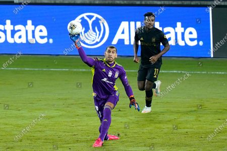 Tigres goalkeeper Nahuel Guzman, left, clears the ball from the goal, in front of Los Angeles FC midfielder Jose Cifuentes during the first half of a CONCACAF Champions League soccer match, in Orlando, Fla