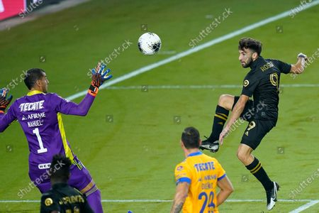 Stock Picture of Los Angeles FC forward Diego Rossi, right, scores a goal with a kick over the head of Tigres goalkeeper Nahuel Guzman (1) during the second half of a CONCACAF Champions League soccer match, in Orlando, Fla