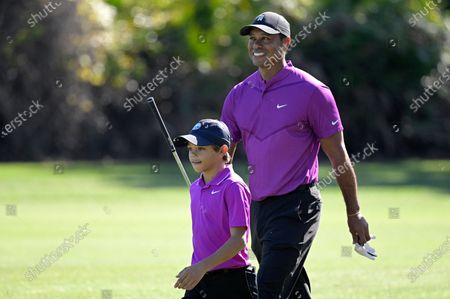 Tiger Woods, right, and his son Charlie walk on the third fairway during the first round of the PNC Championship golf tournament, in Orlando, Fla