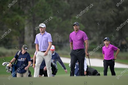 Justin Thomas, left, Tiger Woods, center, and his son Charlie walk to the 18th green during the first round of the PNC Championship golf tournament, in Orlando, Fla