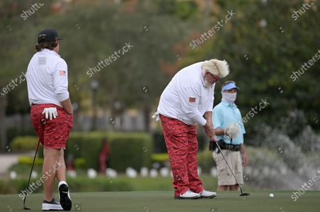 Little John Daly, left, watches as his father John Daly putts on the 18th green during the first round of the PNC Championship golf tournament, in Orlando, Fla