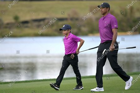Tiger Woods, right, and his son Charlie walk on the 16th fairway during the first round of the PNC Championship golf tournament, in Orlando, Fla