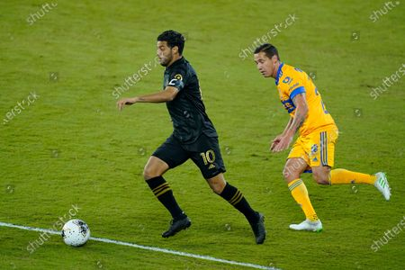 Los Angeles FC forward Carlos Vela (10) gets in front of Tigres midfielder Jesus Duenas, right, during the first half of a CONCACAF Champions League soccer match, in Orlando, Fla