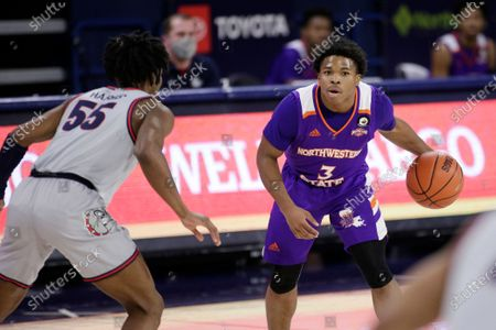 Northwestern State guard Brian White (3) dribbles the ball while pressured by Gonzaga guard Dominick Harris (55) during the first half of an NCAA college basketball game in Spokane, Wash
