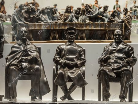 A group of three leaders of the anti-Hitler coalition next to the image of Jesus Christ and the apostles at the Last Supper. Statuettes of Franklin D. Roosevelt, Joseph Stalin  and Winston Churchilll on the showcase of a souvenir shop.