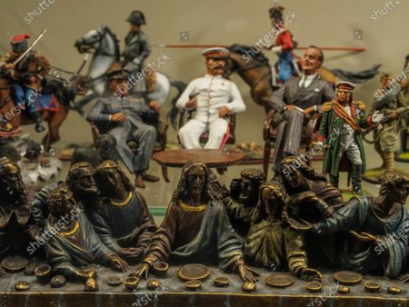 Stock Photo of Bronze image of Jesus Christ and the apostles at the Last Supper against the background of miniature figures of the three leaders of the anti-Hitler coalition and other historical characters. Statuettes of Franklin D. Roosevelt, Joseph Stalin  and Winston Churchilll on the showcase of a souvenir shop.