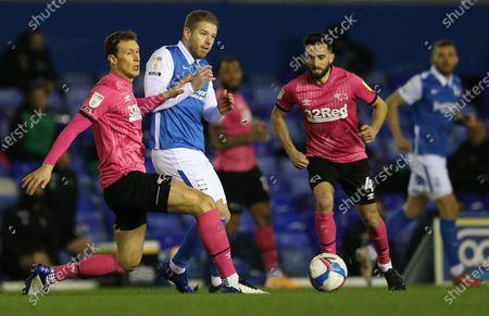 Adam Clayton of Birmingham City is challenged by Krystian Bielik of Derby County
