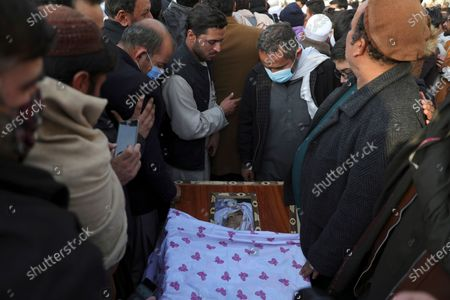 People gather around the body of Mohammad Yousuf Rasheed, executive director of the non-governmental Free and Fair Election Forum of Afghanistan, during his funeral ceremony, in Kabul, Afghanistan, . Separate bombing and shooting attacks in Afghanistan's capital left several people dead Wednesday, including Rasheed, the head of the independent elections watchdog, officials said