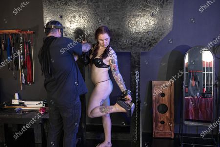 Stock Picture of Dungeon Master, Prof (L) and submissive play partner Miss Kaz (R) during a BDSM play session at the Fetish Heaven dungeon in  Johannesburg, South Africa, 23 December 2020. The Covid-19 disease caused by the novel SARS-CoV-2 coronavirus has had a huge impact on the BDMS subculture in the city with the first months of lockdown starting in March 2020 stopping all events at the dungeon and bringing it to a close. Recently however, relaxation in lockdown restrictions have seen a increase in events and play sessions at the dungeon as people feel the need to deal with the stress and anxiety of the lockdown by visiting the dungeon and playing out their fantasies. Full Covid-19 safety measures are enforced at all times.