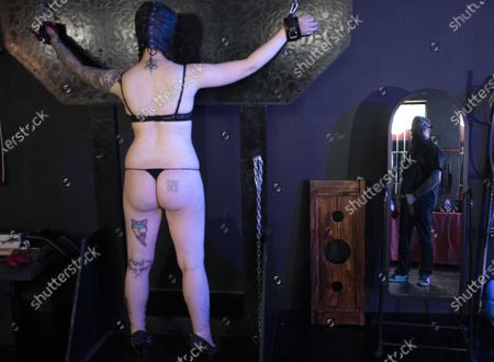 Stock Photo of Dungeon Master, Prof (R) and submissive play partner Miss Kaz (L) during a BDSM play session at the Fetish Heaven dungeon in  Johannesburg, South Africa, 23 December 2020. The Covid-19 disease caused by the novel SARS-CoV-2 coronavirus has had a huge impact on the BDMS subculture in the city with the first months of lockdown starting in March 2020 stopping all events at the dungeon and bringing it to a close. Recently however, relaxation in lockdown restrictions have seen a increase in events and play sessions at the dungeon as people feel the need to deal with the stress and anxiety of the lockdown by visiting the dungeon and playing out their fantasies. Full Covid-19 safety measures are enforced at all times.
