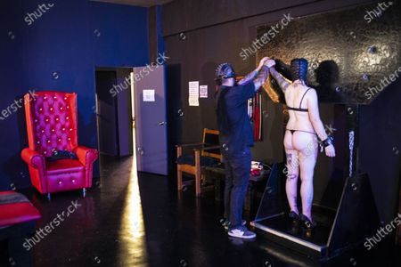 Dungeon Master, Prof (L), straps submissive play partner Miss Kaz (R) during a BDSM play session at the Fetish Heaven dungeon in  Johannesburg, South Africa, 23 December 2020. The Covid-19 disease caused by the novel SARS-CoV-2 coronavirus has had a huge impact on the BDMS subculture in the city with the first months of lockdown starting in March 2020 stopping all events at the dungeon and bringing it to a close. Recently however, relaxation in lockdown restrictions have seen a increase in events and play sessions at the dungeon as people feel the need to deal with the stress and anxiety of the lockdown by visiting the dungeon and playing out their fantasies. Full Covid-19 safety measures are enforced at all times.