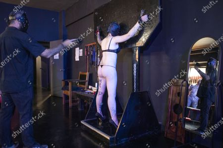 Dungeon Master, Prof (L) and submissive play partner Miss Kaz (R) during a BDSM play session at the Fetish Heaven dungeon in  Johannesburg, South Africa, 23 December 2020. The Covid-19 disease caused by the novel SARS-CoV-2 coronavirus has had a huge impact on the BDMS subculture in the city with the first months of lockdown starting in March 2020 stopping all events at the dungeon and bringing it to a close. Recently however, relaxation in lockdown restrictions have seen a increase in events and play sessions at the dungeon as people feel the need to deal with the stress and anxiety of the lockdown by visiting the dungeon and playing out their fantasies. Full Covid-19 safety measures are enforced at all times.