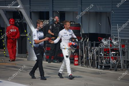 Jenson Button, McLaren walks back to the garage with Michael Collier 'Mikey Muscles'.