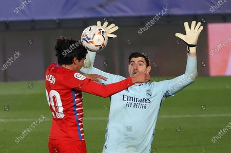 Real Madrid's goalie Thibaut Courtois (R) in action against Granada CF's Jesus Vallejo (L) during a Spanish LaLiga soccer match between Real Madrid and Granada CF at Alfredo Di Stefano stadium in Madrid, Spain, 23 December 2020.