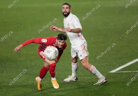 Granada's Carlos Neva, left, eyes the ball as he challenges Real Madrid's Dani Carvajal during the Spanish La Liga soccer match between Real Madrid and Granada at the Alfredo Di Stefano stadium in Madrid, Spain