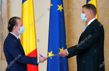 Romanian new Prime Minister Florin Catu (L) shakes hands with Romanian President Klaus Iohannis (R) during the swearing in ceremony held at the Presidential Palace, in Bucharest, Romania, 23 December 2020. Catu, former Finance Minister, was nominated as prime minister by the Romanian president Klaus Iohannis. Catu's cabinet passed parliament with a final score of 260 at 186 votes.