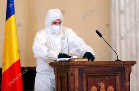 A sanitary worker disinfects the signing desk and the bible after each cabinet member, during the swearing in ceremony for the new Prime Minister Florin Catu held at the Presidential Palace, in Bucharest, Romania, 23 December 2020. Catu, former Finance Minister, was nominated as prime minister by the Romanian president Klaus Iohannis. Catu's cabinet passed parliament with a final tally of 260 for and 186 votes against.