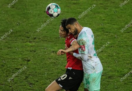 Genki Haraguchi of Hannover (L) in action against  Bremen's Jean-Manuel Mbom during the German DFB Cup second round soccer match between Hannover 96 and Werder Bremen in Hanover, Germany, 23 December 2020.