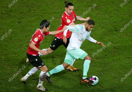 Stock Picture of (L-R) Genki Haraguchi of Hannover and Valmir Sulejmani of Hannover in action against Bremen's Jean-Manuel Mbom during the German DFB Cup second round soccer match between Hannover 96 and Werder Bremen in Hanover, Germany, 23 December 2020.