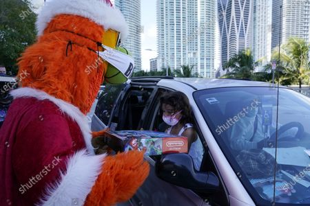 Gabriela Lopez, 6, right, receives a gift from the Miami Heat mascot Burnie during a food and gift distribution to Miami-Dade County students and their families who are in need, in Miami. The event was hosted by the Miami Heat NBA basketball team and other organizations