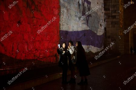 Three young women pose for a selfie with projections of the national flags of Israel and Morocco on the walls of the Old City of Jerusalem, . Senior White House adviser Jared Kushner led a delegation from Israel to Morocco on Tuesday on the first known direct flight since the two countries agreed to establish full diplomatic ties earlier this month as part of a series of U.S.-brokered normalization accords with Arab countries