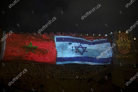 """The national flags of Israel and Morocco are projected on the walls of the Old City of Jerusalem, along with the word """"peace,"""" in English, Hebrew, and Arabic. Senior White House adviser Jared Kushner led a delegation from Israel to Morocco on Tuesday on the first known direct flight since the two countries agreed to establish full diplomatic ties earlier this month as part of a series of U.S.-brokered normalization accords with Arab countries"""