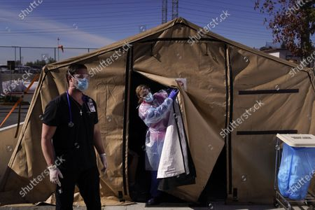 Stock Picture of Registered nurse Keith Robinson, right, watches as fellow nurse Angela Coomds calls out a patient's name from a COVID-19 triage tent at Providence Holy Cross Medical Center in the Mission Hills section of Los Angeles