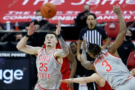 Ohio State forward Kyle Young, left, and guard Eugene Brown, right, work for a rebound against Rutgers guard Paul Mulcahy during an NCAA college basketball game in Columbus, Ohio, . Ohio State won 80-68