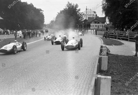 Hermann Lang, Mercedes-Benz W154 (#16), leads Rudolf Caracciola, Mercedes-Benz W154 (#14), and Manfred von Brauchitsch, Mercedes-Benz W154 (#10), as the rest of the field follows behind.