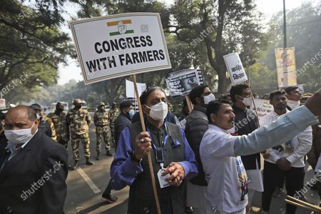 Congress party leader Shashi Tharoor holds a placard during a protest against new agricultural laws in New Delhi, India, . Congress party leaders met Indian President Ram Nath Kovind Thursday and demanded withdrawal of new agricultural laws that have stoked widespread anger among the farmers