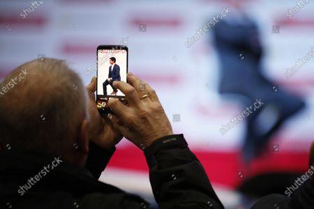 A fan takes a photo of Karun Chandhok on stage