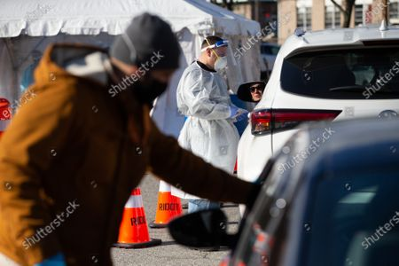 Medical personnel administer COVID-19 tests at a drive-through testing site in the parking lot of McCoy Stadium in Pawtucket, Rhode Island on Thursday, December 10, 2020. The state currently has the highest per capita COVID-19 rate in the country.