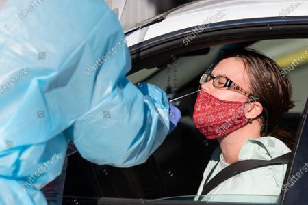 Morgan Adamonis of Seekonk, Massachusetts has her nose swabbed for a COVID-19 tests in the parking lot of McCoy Stadium in Pawtucket, Rhode Island on Thursday, December 10, 2020. The state currently has the highest per capita COVID-19 rate in the country.