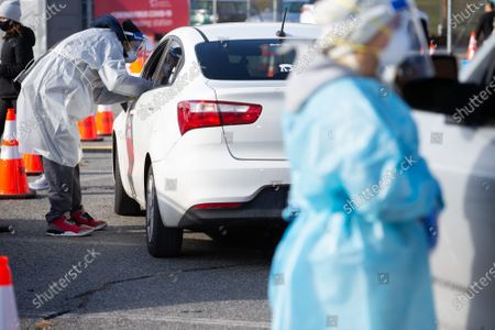 Stock Photo of Medical personnel administer COVID-19 tests at a drive-through COVID testing site in the parking lot of McCoy Stadium in Pawtucket, Rhode Island on Thursday, December 10, 2020. The state currently has the highest per capita COVID-19 rate in the country.