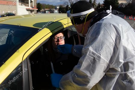 Susanna Draine (L) of Providence, Rhode Island has her nose swabbed by medical worker Jim Melia for a COVID-19 tests in the parking lot of McCoy Stadium in Pawtucket, Rhode Island on Thursday, December 10, 2020. The state currently has the highest per capita COVID-19 rate in the country.