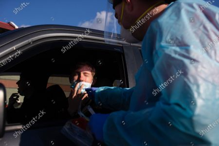 Conor Murphy (L) of Providence, Rhode Island has his nose swabbed for a COVID-19 test by medical worker Matthew Martell at a drive-through COVID testing site in the parking lot of McCoy Stadium in Pawtucket, Rhode Island on Thursday, December 10, 2020. The state currently has the highest per capita COVID-19 rate in the country.