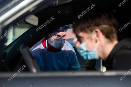 Medical worker Matthew Martell (L) chats with Joseph Murphy (obscured) and brother Conor Murphy (R) at a drive-through COVID-19 testing site in the parking lot of McCoy Stadium in Pawtucket, Rhode Island on Thursday, December 10, 2020. The state currently has the highest per capita COVID-19 rate in the country.