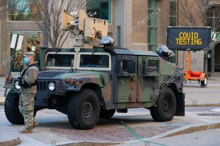 Stock Picture of A member of the Rhode Island National guard stands by at the entrance to a drive-through COVID-19 testing site in downtown Providence, Rhode Island on Thursday, December 10, 2020. The state currently has the highest per capita COVID-19 rate in the country.