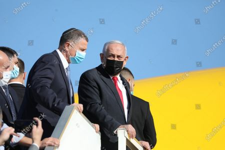 Israeli Prime Minister Benjamin Netanyahu (R) and his Health Minister Yuli-Yoel Edelstein (L) attend the arrival of the first batch of more than 100,000 doses of Pfizer vaccines after they land at Ben Gurion Airport near Tel Aviv, Israel. The Israeli COVID-19 immunization program is to begin within two weeks.
