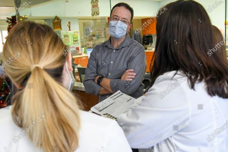 Dr. Michael Roberts, center, chief of staff at East Alabama Medical Center, talks with a pharmacist during rounds in the intensive care unit, in Opelika, Ala