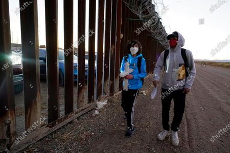 Nathan Adams Maldonado, left, and Caleb Dupree, an intern for Frontera de Cristo, walk along the border fence, as asylum seeking families on the Mexico side participate in a Las Posadas event at the U.S.-Mexico border wall with Maldonado, Dupree and a small group on the U.S. side, in Douglas, Ariz. People on each side of the border celebrate Las Posadas as they have done for decades, a centuries-old tradition practiced in Mexico re-enacts Mary and Joseph's search for refuge in Bethlehem through songs, with several of the families attending stuck south of the border, their lives in limbo with U.S. proceedings suspended amid the COVID pandemic