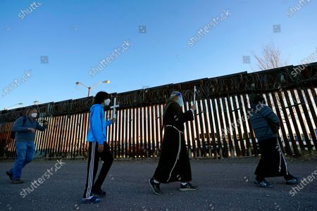From left to right, Mark Adams, PCUSA Mission Co-worker serving with Frontera de Cristo, Nathan Adams Maldonado, Brother David Buer, and Father Oscar Mejia, walk in front of the border fence during a procession to the border as part of a Las Posadas event with several asylum seeking families at the U.S.-Mexico border wall, in Douglas, Ariz. People on each side of the border celebrate Las Posadas as they have done for decades, a centuries-old tradition practiced in Mexico re-enacts Mary and Joseph's search for refuge in Bethlehem through songs, with the families attending stuck south of the border, their lives in limbo with U.S. proceedings suspended amid the COVID pandemic