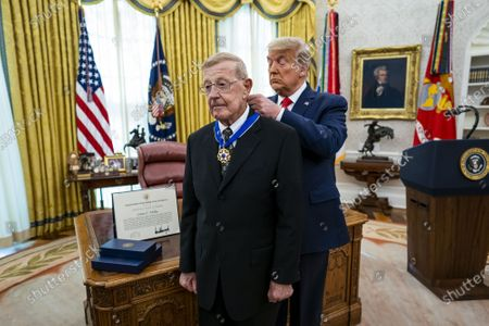 President Donald Trump presents the Medal of Freedom to Lou Holtz in the Oval Office at the White House in Washington, DC on Thursday, December 3, 2020.