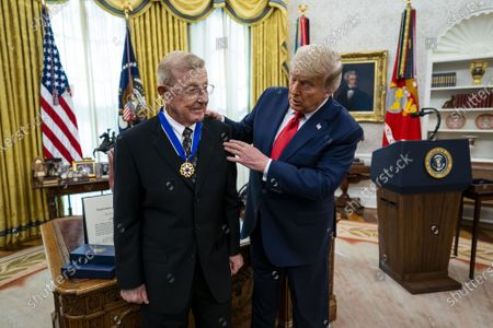 Stock Picture of President Donald Trump presents the Medal of Freedom to Lou Holtz in the Oval Office at the White House in Washington, DC on Thursday, December 3, 2020.