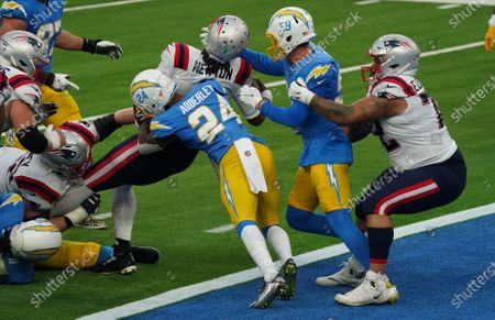 New England Patriots Cam Newton (L) scores through Los Angeles Chargers Nasir Adderley(24) in second quarter action at SoFi Stadium in Inglewood, California on Sunday, December 6, 2020. The Patriots lead the Chargers 28-0 at halftime.