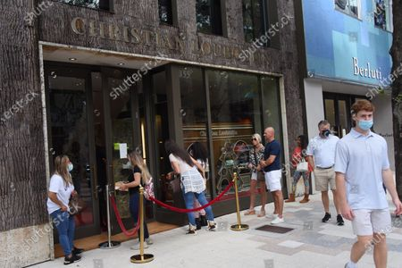 Stock Image of Dec. 24 2020- People are seen waiting in line to go into Christian Louboutin. Shoppers are seen on Christmas Eve at the Miami Design District