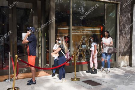 Dec. 24 2020- People are seen waiting in line to go into Christian Louboutin. Shoppers are seen on Christmas Eve at the Miami Design District